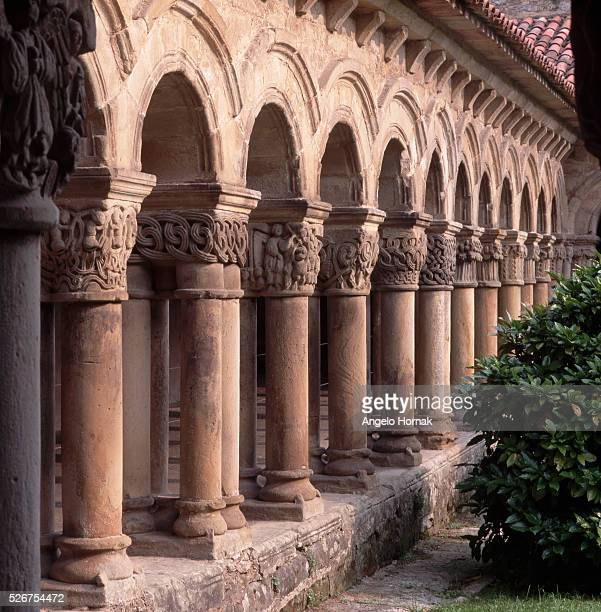 Carved strapwork patterns and foliate motifs embellish the late 12th century Romanesque capitals in a cloister of the Santillana del Mar's 12th...