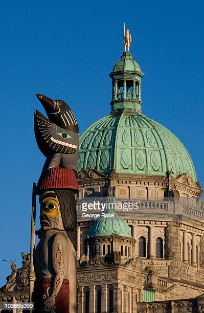 A carved wood totem pole stands in contrast to the ornate Parliment Building on July 4 2010 in Victoria British Columbia Canada Victoria a major...