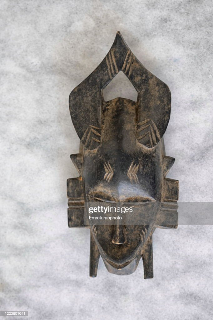 Carved wooden African tribe mask on gray marble table top. : Stock Photo