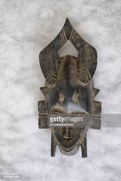 carved wooden african tribe mask on gray marble table top. - emreturanphoto stock pictures, royalty-free photos & images