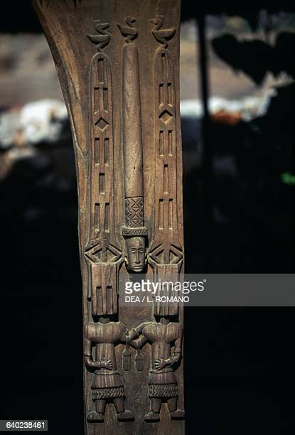 Carved wooden pole from a toguna depicting a ritual mask meeting house for the elders at the centre of a Dogon village with the Bandiagara Escarpment...