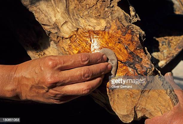 Carver putting oil on a piece of olive wood, Provence, Frankreich