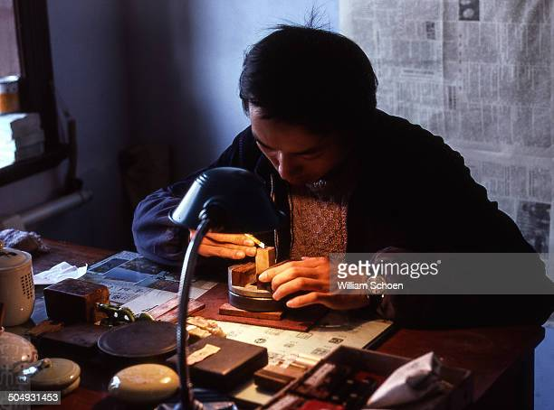 Carving a chop or stamp. Man working in a factory that makes Chinese Chops or seals to afix to artwork, legal documents or for use a signature.