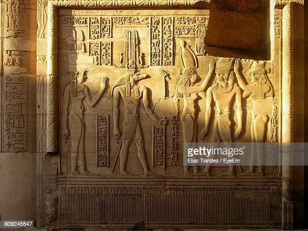 carvings on wall at ancient temple - egyptian culture stock photos and pictures