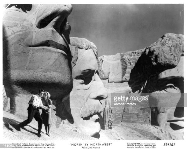 Cary Grant and Eva Marie Saint walking near the faces on Mt Rushmore in a scene from the film 'North By Northwest' 1959