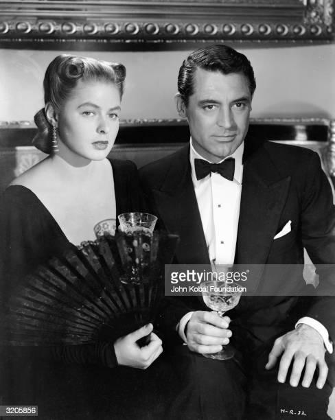 Cary Grant and Ingrid Bergman share a drink in Alfred Hitchcock's spy thriller 'Notorious'.