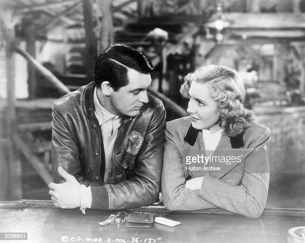 Cary Grant and Jean Arthur standing against a counter with their arms folded in front of them in a scene from 'Only Angels Have Wings' Title Only...