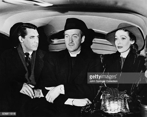 Cary Grant as the angel Dudley David Niven as Bishop Henry Brougham and Loretta Young as Julia Brougham ride in a car in the 1947 film The Bishop's...