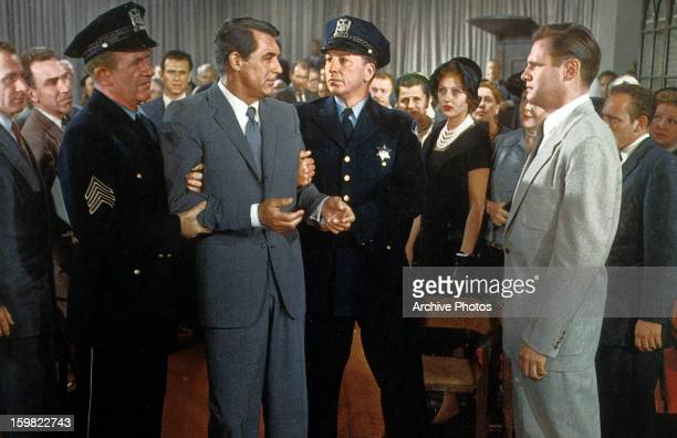 Cary Grant is restrained by two officers in a scene from the film 'North By Northwest' 1959