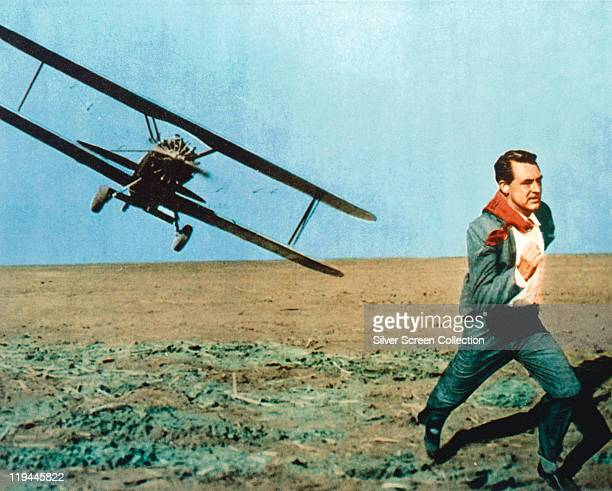 Cary Grant running as he comes under attack from a biplane under attack in an iconic scene issued as a publicity still for the film 'North by...