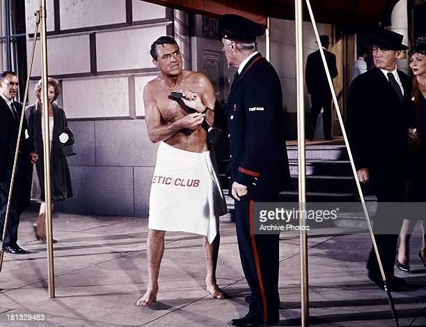 Cary Grant stands outside wearing a towel in a scene from the film 'That Touch Of Mink' 1962