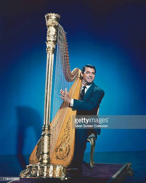 Cary Grant wearing a blue suit as he sits playing a harp against a blue background in a publicity still issued for the film 'The Bishop's Wife' USA...