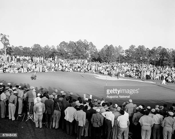 Cary Middlecoff hits out of a bunker before a large gallery during the 1956 Masters Tournament at Augusta National Golf Club on April 7 1956 in...