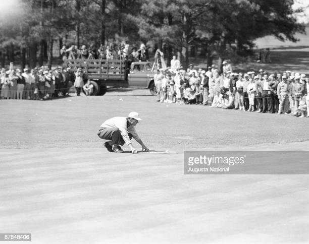 Cary Middlecoff lines up his putt in front of a large gallery during the 1956 Masters Tournament at Augusta National Golf Club in April 1956 in...
