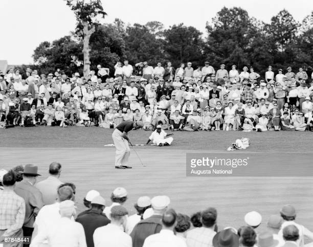Cary Middlecoff putts as a large gallery watches during the 1956 Masters Tournament at Augusta National Golf Club in April 1956 in Augusta Georgia
