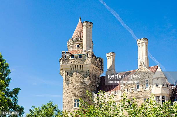 Casa Loma an example of a Medieval Castle and Gothic Revival architecture: tower hit by bright sunlight under a clear blue sky.