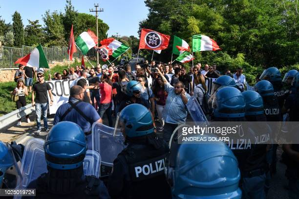 CasaPound far-right wing activists are watched by police officials as they protest the arrival of migrants at the Catholic Church centre 'Mondo...
