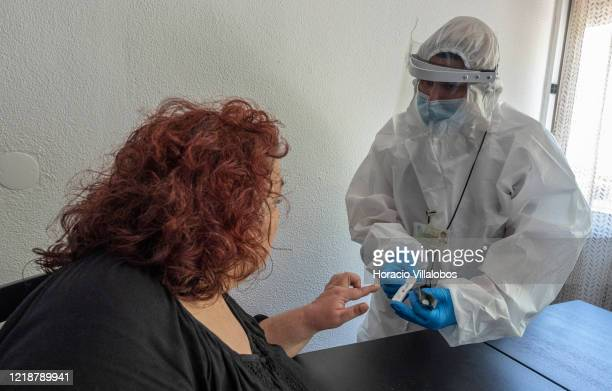 Cascais resident Rosario Sezero reacts while being pricked in the finger for a sample of capillary blood by a paramedic testing residents at their...
