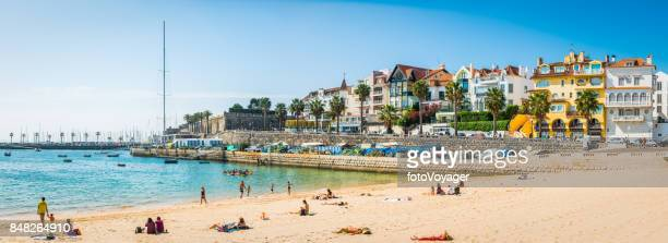 cascais sunbathers on ocean beach vacation resort panorama lisbon portugal - cascais stock photos and pictures
