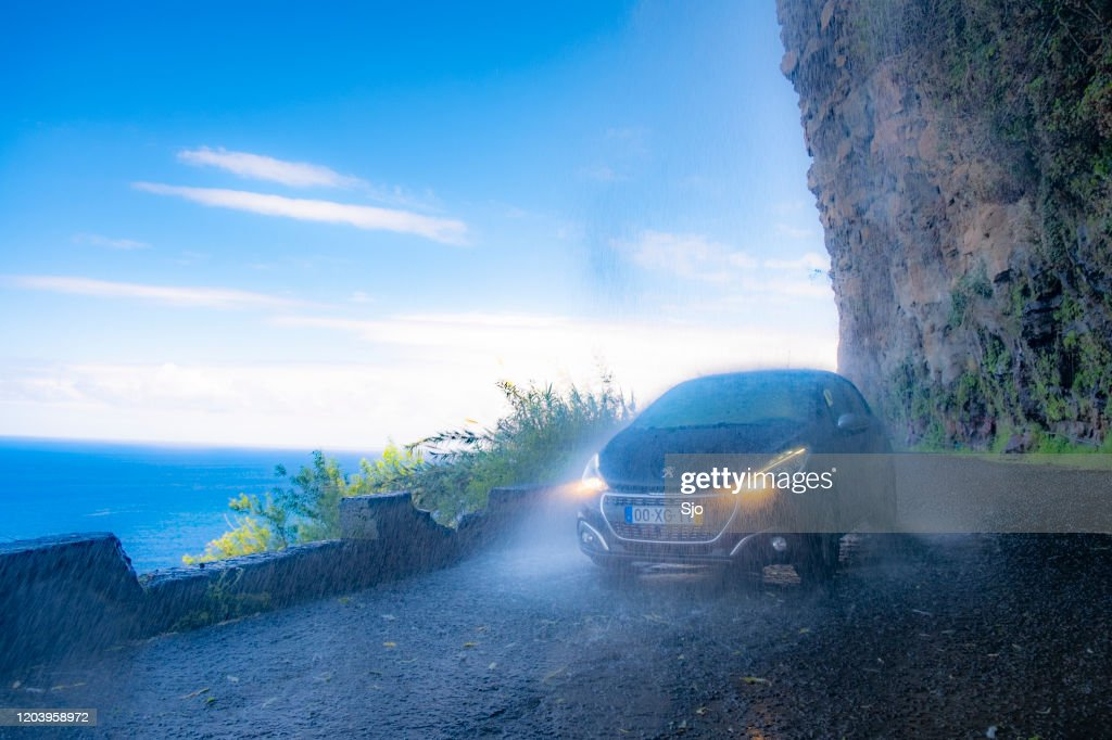 Cascata dos Anjos waterfall on the coastal road of Madeira island with a car driving through the falling water : Stock Photo