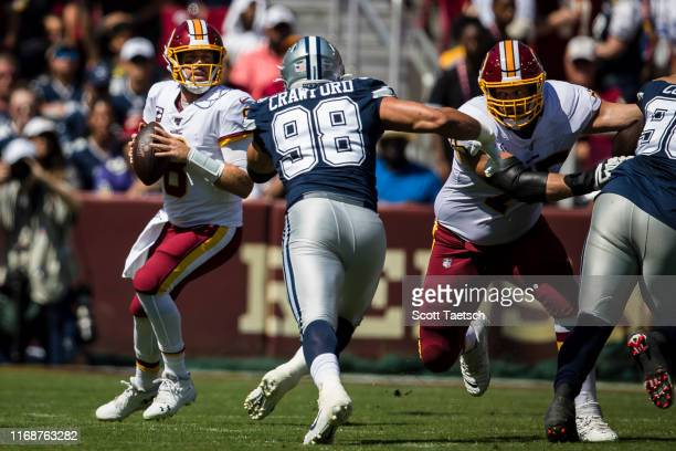 Case Keenum of the Washington Redskins drops back to pass as Tyrone Crawford of the Dallas Cowboys applies pressure during the first half at...