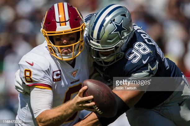 Case Keenum of the Washington Redskins is sacked by Tyrone Crawford of the Dallas Cowboys during the first half at FedExField on September 15 2019 in...