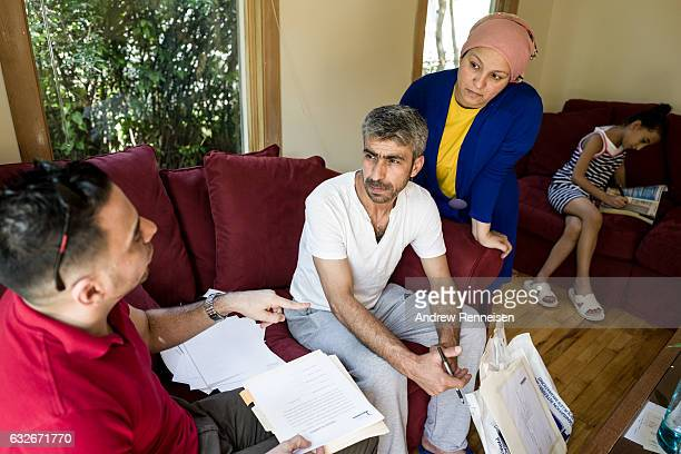 A case worker goes over paper work with the Tanbal Family in their new home on July 27 2015 in Bloomfield Hills Michigan Since the war started the...
