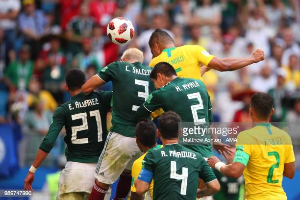 Casemiro of Brazil goes up for a header with Carlos Salcedo and Hugo Ayala of Mexico during the 2018 FIFA World Cup Russia Round of 16 match between...