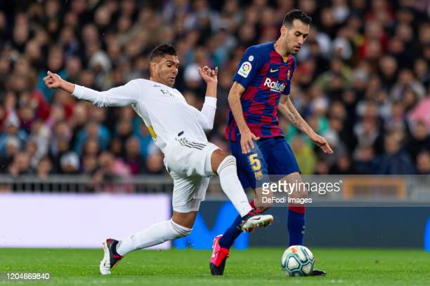 Casemiro of Real Madrid and Sergio Busquets of FC Barcelona battle for the ball during the Liga match between Real Madrid CF and FC Barcelona at...