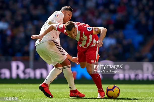 Casemiro of Real Madrid competes for the ball with Alex Granell of Girona FC during the La Liga match between Real Madrid CF and Girona FC at Estadio...