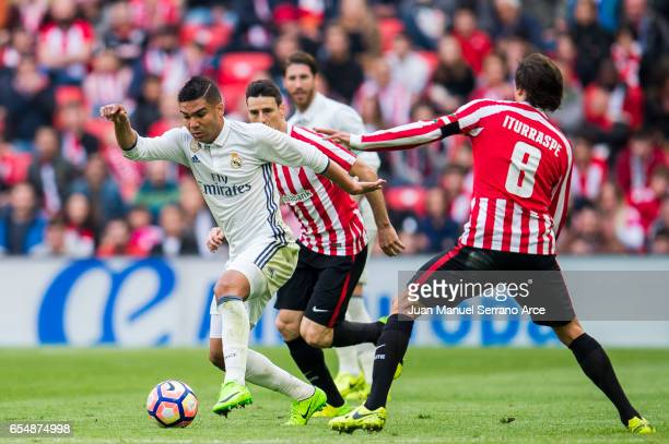 Casemiro of Real Madrid competes for the ball with Ander Iturraspe of Athletic Club during the La Liga match between Athletic Club Bilbao and Real...