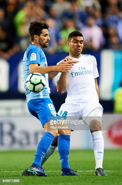 Casemiro of Real Madrid competes for the ball with Manuel Adrian Gonzalez of Malaga during the La Liga match between Malaga CF and Real Madrid CF at...