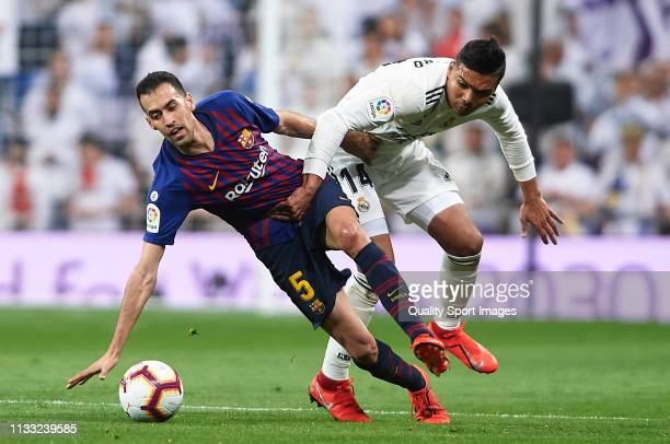 Casemiro of Real Madrid competes for the ball with Sergio Busquets of Barcelona during the La Liga match between Real Madrid CF and FC Barcelona at...