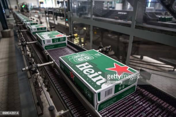 Cases of Heineken beer move along a conveyor at the Heineken NV brewery in Yangon Myanmar on June 15 2017 Heineken is seeking to exploit the...