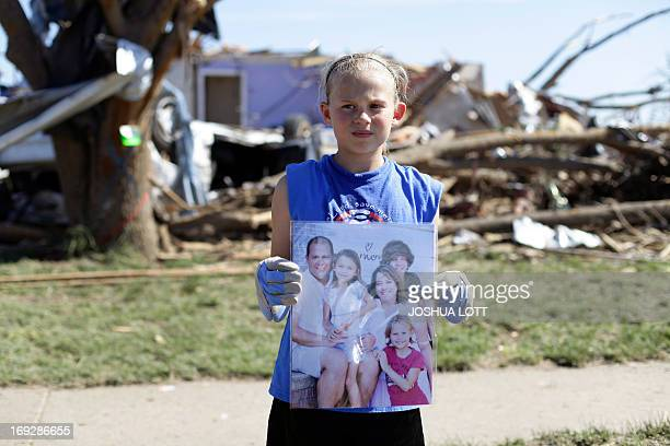 Casey Angle a student at Plaza Towers Elementary School poses for a portrait outside her destroyed home as she holds a family photo that includes her...