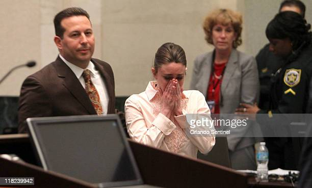 Casey Anthony, with her attorney Jose Baez, left, approaches the podium to hear Judge Belvin Perry confirm that she is not guilty of murder charges...