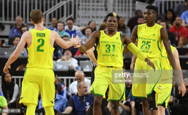 Casey Benson of the Oregon Ducks highfives teammate Dylan Ennis as Chris Boucher looks on during a semifinal game of the Pac12 Basketball Tournament...