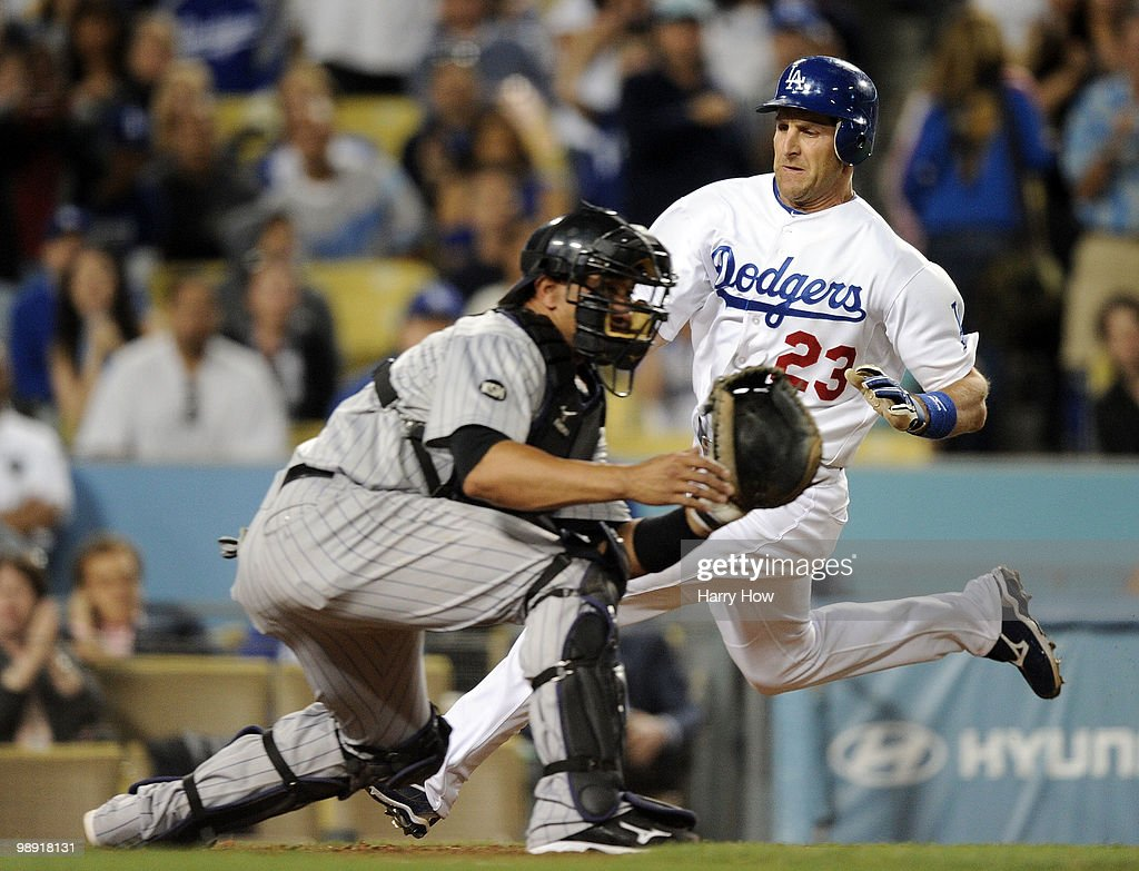 Casey Blake #23 of the Los Angeles Dodgers scores a run around Miguel Olivo #21 of the Colorado Rockies for a 5-3 lead during the fifth inning at Dodger Stadium on May 7, 2010 in Los Angeles, California.