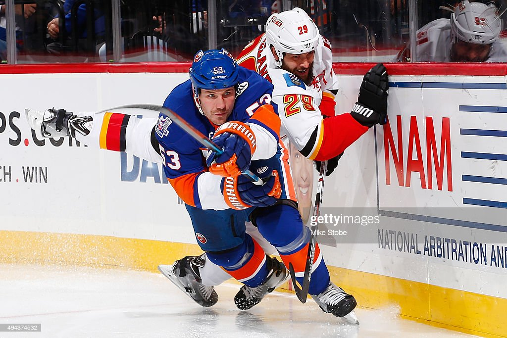 Casey Cizikas #53 of the New York Islanders and Deryk Engelland #29 of the Calgary Flames battle against the boards during the game at the Barclays Center on October 26, 2015 in Brooklyn borough of New York City.
