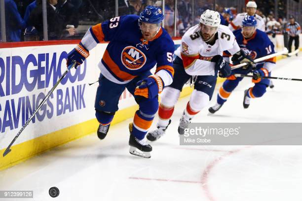 Casey Cizikas of the New York Islanders and Keith Yandle of the Florida Panthers chase down a loose puck during the second period at Barclays Center...