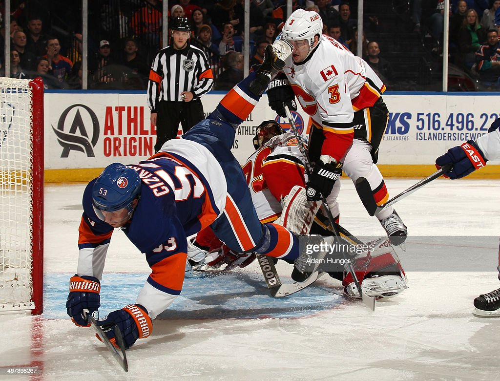 Casey Cizikas #53 of the New York Islanders and Ladislav Smid #3 of the Calgary Flames get tripped up by Reto Berra #29 of the Calgary Flames during the second period at Nassau Coliseum on February 6, 2014 in Uniondale, New York.