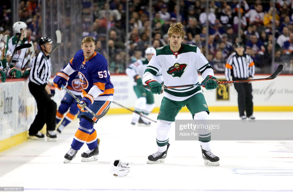Casey Cizikas #53 of the New York Islanders and Marcus Foligno #17 of the Minnesota Wild lose their helmets in the first period during their game at Barclays Center on February 19, 2018 in the Brooklyn borough of New York City.