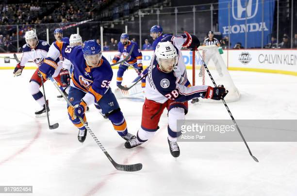 Casey Cizikas of the New York Islanders and Oliver Bjorkstrand of the Columbus Blue Jackets chase after the puck in the first period during their...