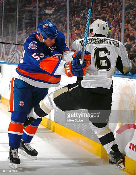 Casey Cizikas of the New York Islanders checks Scott Harrington of the Pittsburgh Penguins into the boards at Nassau Veterans Memorial Coliseum on...