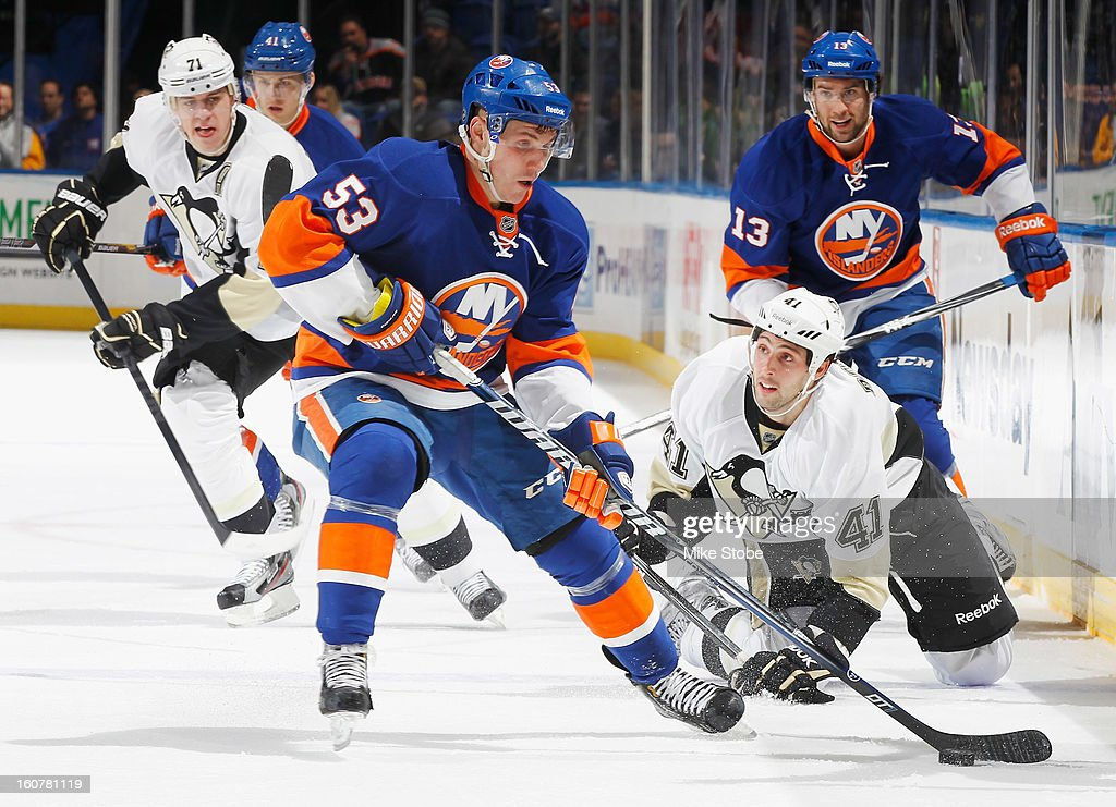 Casey Cizikas #53 of the New York Islanders controls the puck in front of Robert Bortuzzo #41 and Evgeni Malkin #71 of the Pittsburgh Penguins at Nassau Veterans Memorial Coliseum on February 5, 2013 in Uniondale, New York.