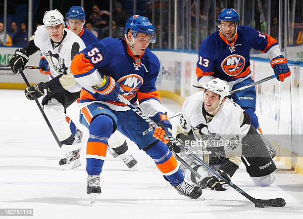 Casey Cizikas of the New York Islanders controls the puck in front of Robert Bortuzzo and Evgeni Malkin of the Pittsburgh Penguins at Nassau Veterans...