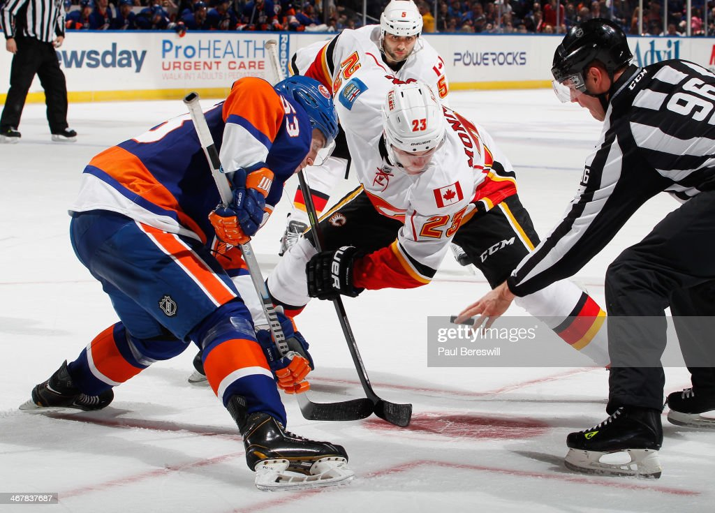 Casey Cizikas #53 of the New York Islanders faces off with Sean Monahan #23 of the Calgary Flames as linesman David Brisebois #96 drops the puck during an NHL hockey game at Nassau Veterans Memorial Coliseum on February 6, 2014 in Uniondale, New York.