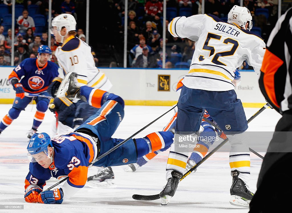 Casey Cizikas #53 of the New York Islanders falls to the ice in front of Alexander Sulzer #52 of the Buffalo Sabres at Nassau Veterans Memorial Coliseum on February 9, 2013 in Uniondale, New York.