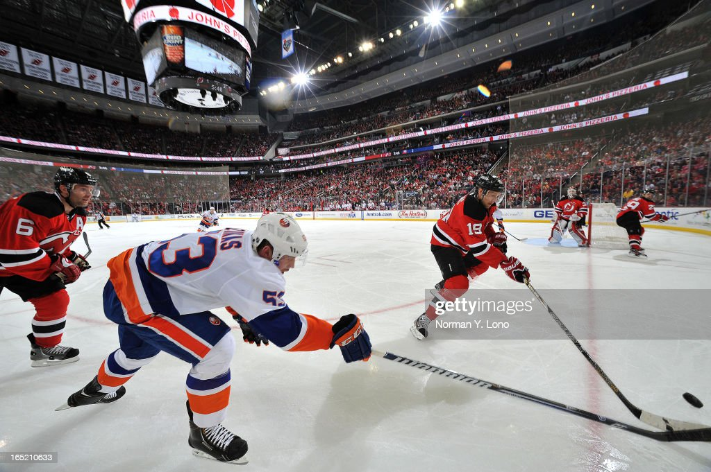 Casey Cizikas #53 of the New York Islanders is barely beaten to the puck by Travis Zajac #19 of the New Jersey Devils at the Prudential Center on April 1, 2013 in Newark, New Jersey. Islanders win 3-1 over the Devils.