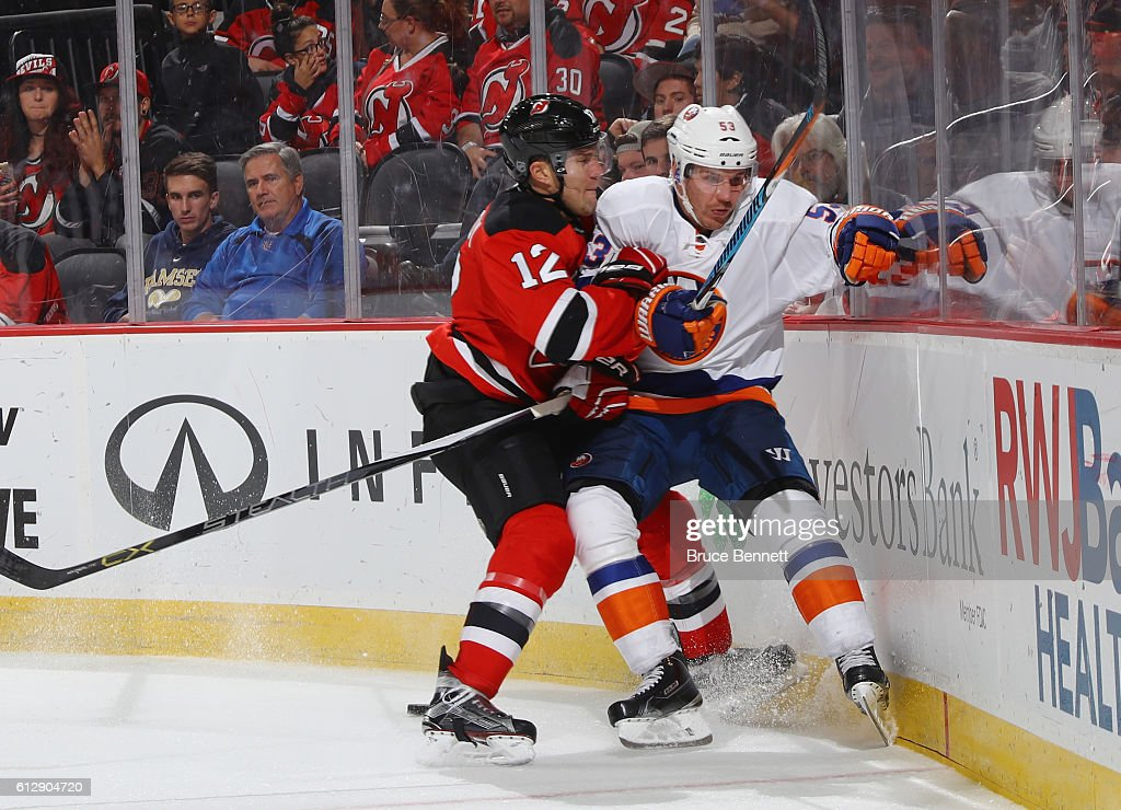 Casey Cizikas #53 of the New York Islanders is ht into the boards by Ben Lovejoy #12 of the New Jersey Devils during the third period at the Prudential Center on October 5, 2016 in Newark, New Jersey. The Islanders defeated the Devils 3-2.